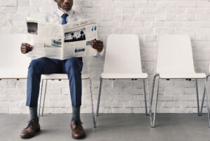 African Businessman Reading Newspaper Workplace Concept